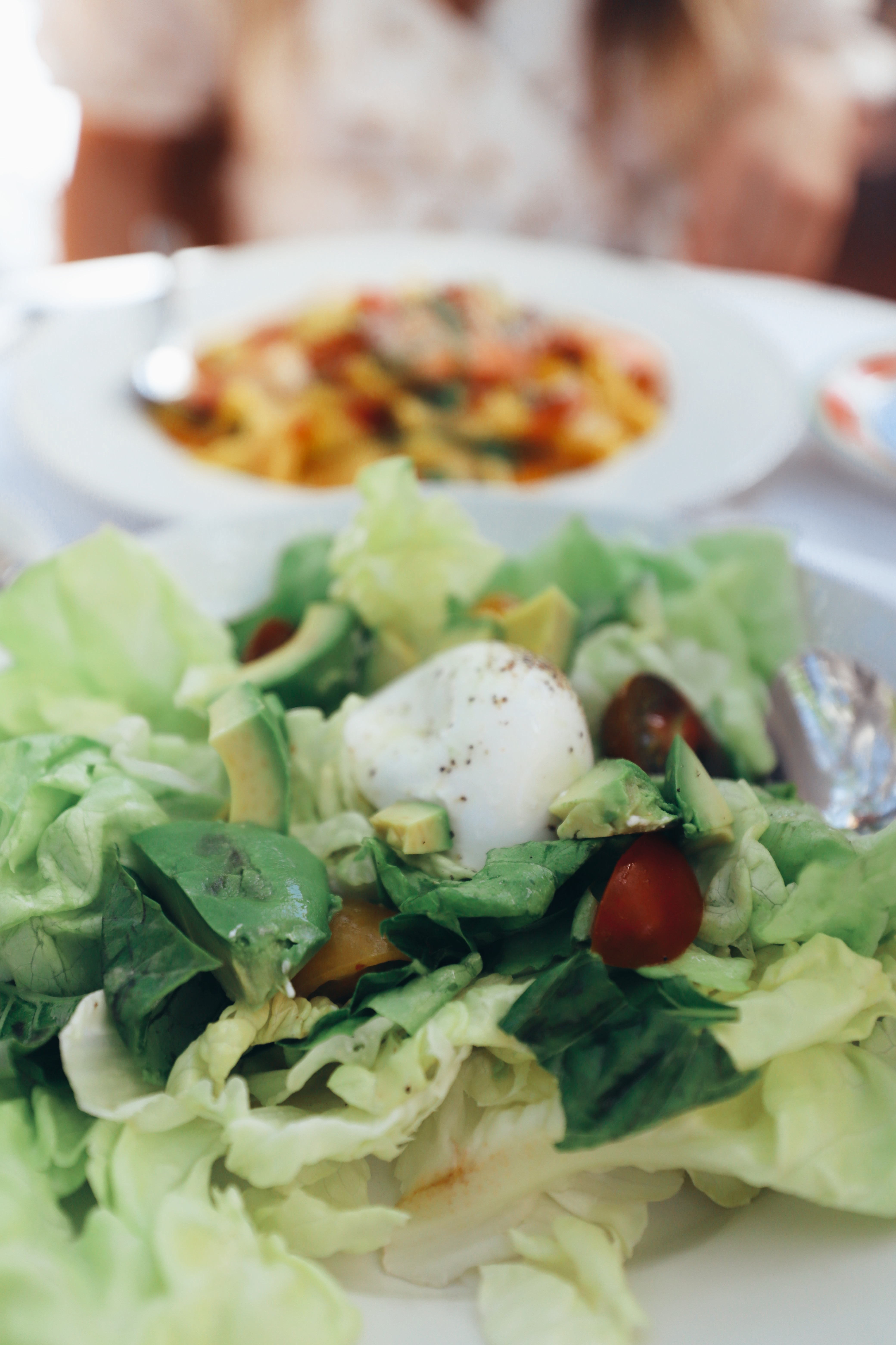 a close up of a salad with egg on it and tomatoes
