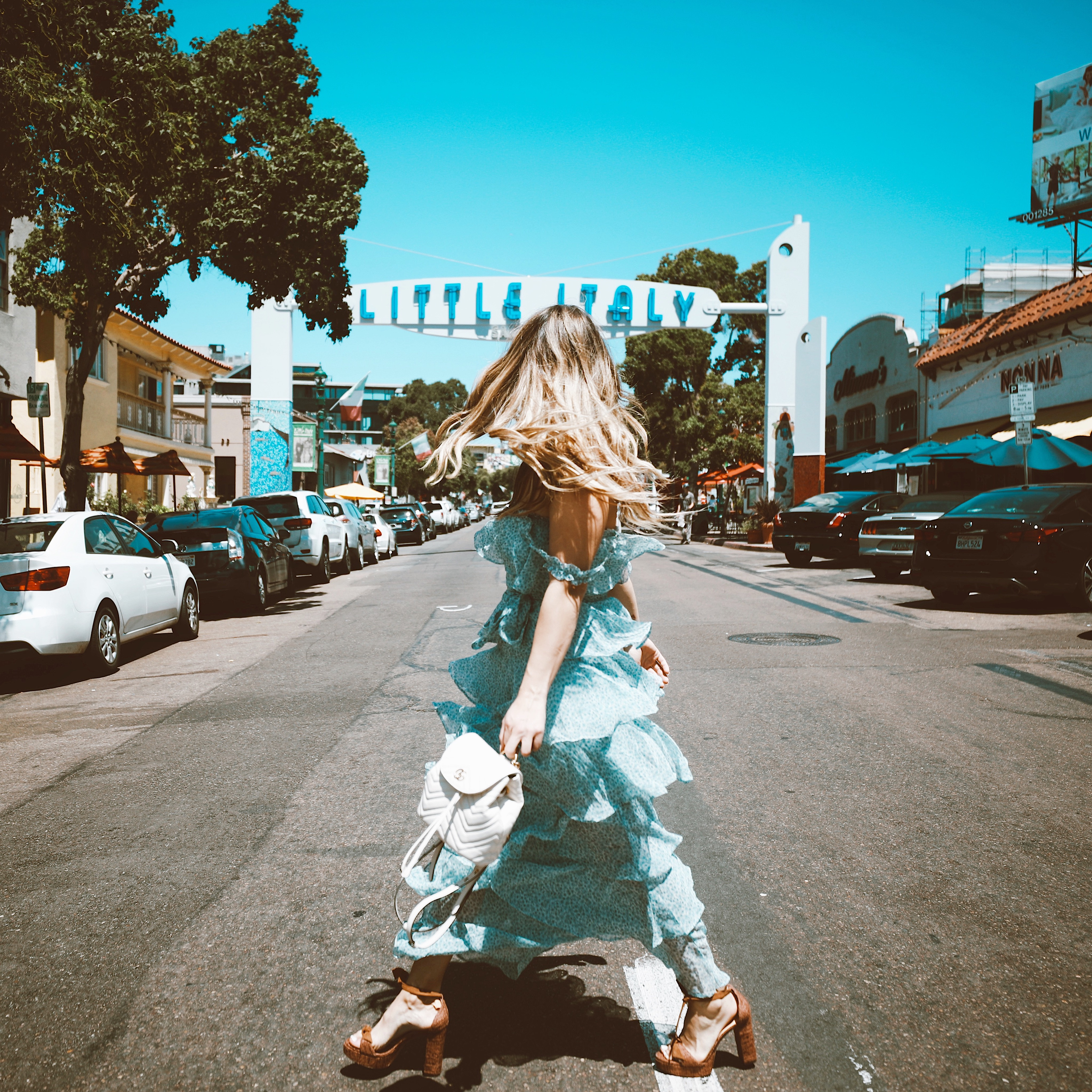 A girl in a dress walking through little italy in san diego, foodies guide la jolla